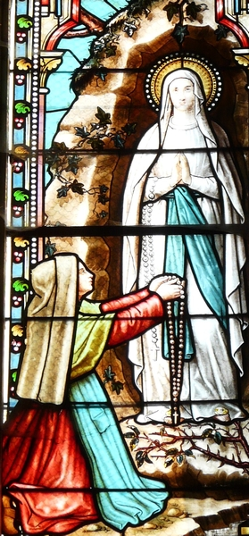 detail of a stained glass window depicting the apparition of the Virgin Mary to Bernadette Soubirous; date and artist unknown; church of Saint-Pierre-ès-Liens, Bourdeilles, Dordogne, France; photographed on 17 December 2009 by Père Igor; swiped from Wikimedia Commons; click for source image