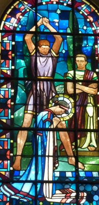 detail of a stained glass window of the martyrdom of Saint Eugenia; date unknown, artist unknown; church of Notre-Dame de Clignancourt, Paris, France; phtographed on 28 August 2010 by GFreihalter; swiped from Wikimedia Commons; click for source image