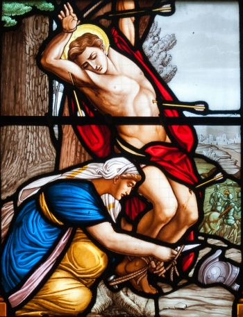 detail of a stained glass window of Saint Irene tending to Saint Sebastian; c.1885 by Hucher et fils succ. fab. du Carmel du Mans; Church of Saint-Martin, Réthoville, Manche, Basse-Normandie, France; photographed on 1 September 2013 by Andreas F. Borchert; swiped from Wikimedia Commons; click for source image