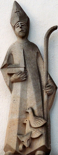 sandstone sculpture of the Saint Liudger; date and artist unknown; eastern facade of Recker Dionysius youth home, parish church of Saint Dionysius, Recke, North Rhine-Westphalia, Germany; photographed in July 2010 by J. H. Janßen; swiped from Wikimedia Commons; click for source image
