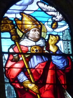 detail of a stained glass window in the cathedral of Our Lady of the Assumption, Segovia Spain, depicting Saint Remegius of Rheims receiving a lamp from a dove; date and artist unknown; photographed on 22 Juuly 2013 by GFreihalter; swiped from Wikimedia Commons; click for source image