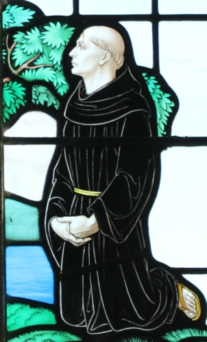 detail of a stained glass window of Saint Tudwal of Tréguier listening to Saint Mawes; date and artist unknown; photographed on 2 October 2015 by Andrewrabbott; swiped from Wikimedia Commons; click for source image