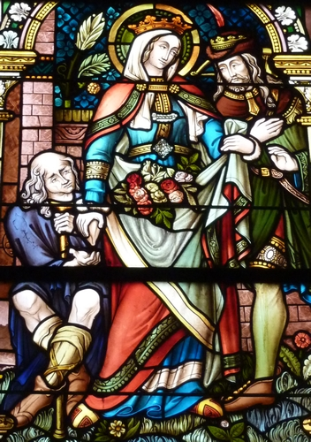 detail of a stained glass window of Saint Elizabeth of Hungary giving alms during the miracle of the roses; late 19th century by Glasmalerei Oidtmann; choir of the church of Saint Martin, Wormersdort, Germany; photographed on 6 October 2010 by Reinhardhauke; swiped from Wikimedia Commons